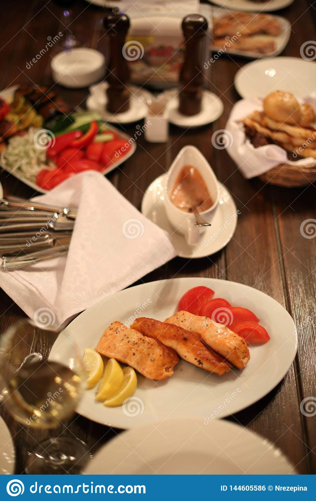 Pieces of grilled salmon on a plate with lemon on the decorated table