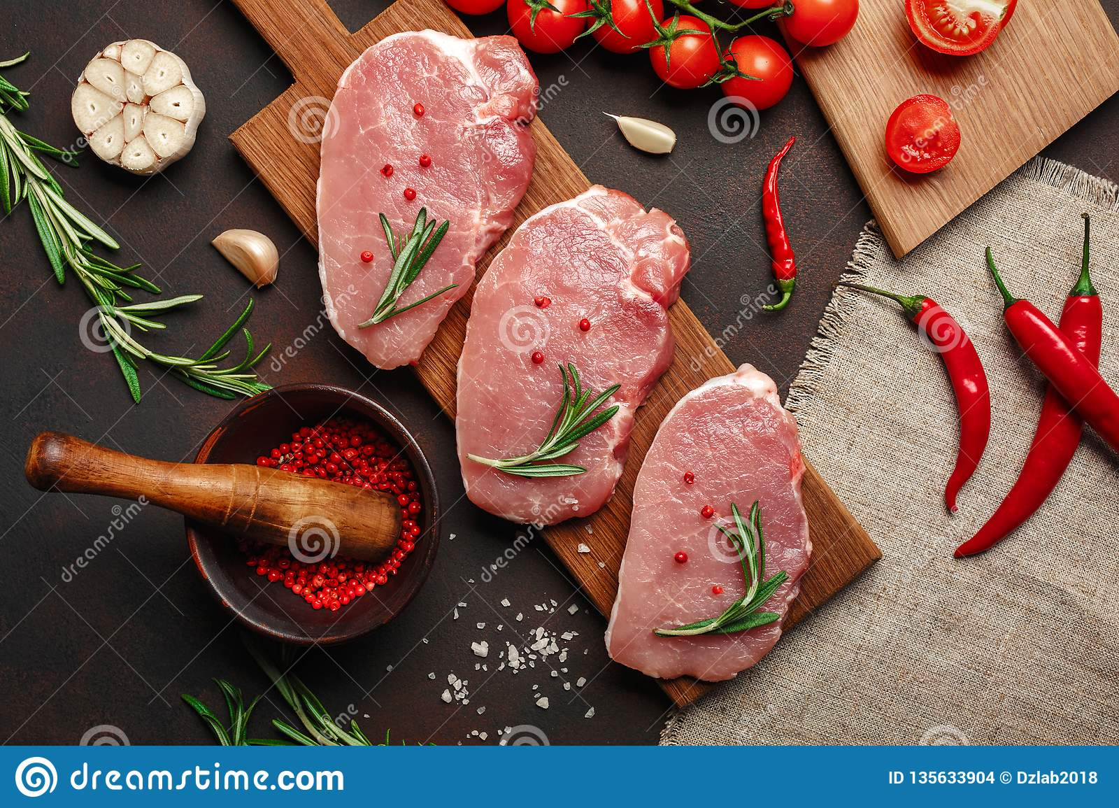 Pieces of raw pork steak on cutting board with cherry tomatoes, rosemary, garlic, pepper, salt and spice mortar on rusty brown