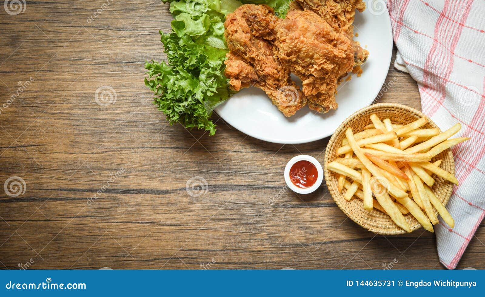 Pieczony kurczak crispy i sałatkowa sałata na bielu talerzu z francuzem smaży koszykowego ketchup na drewnianym łomota stole