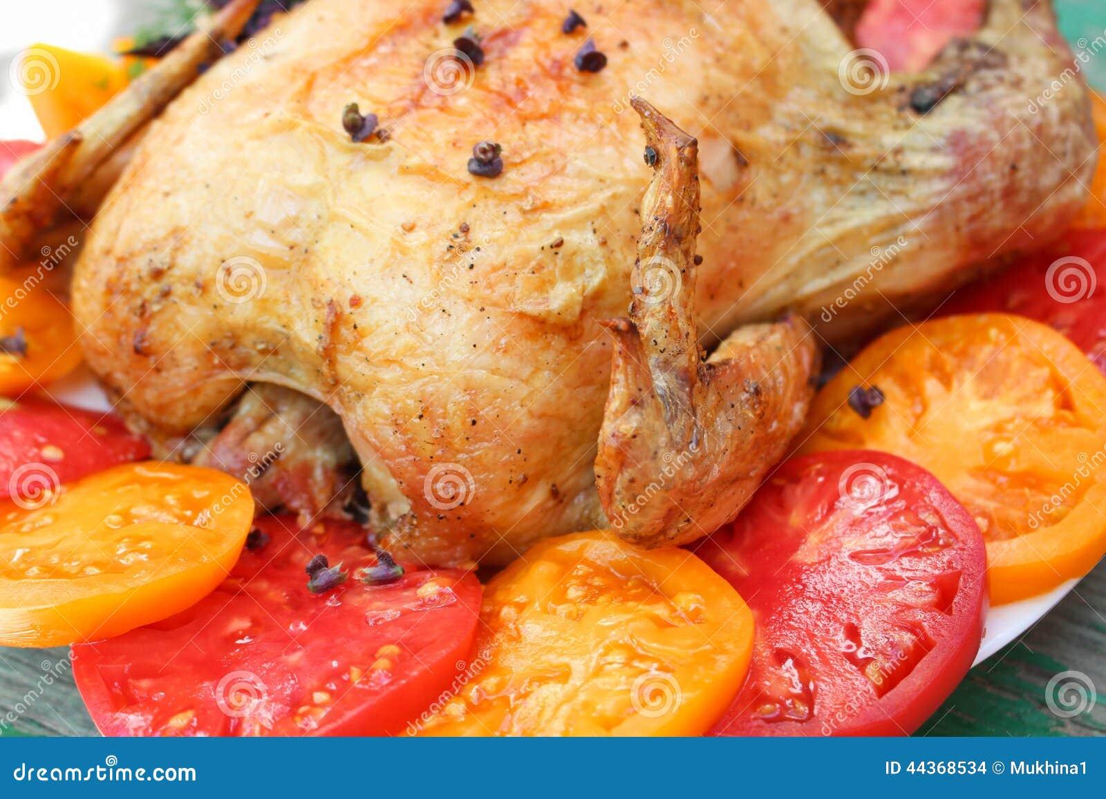 Pieczony kurczak z pomidorami na białym talerzu