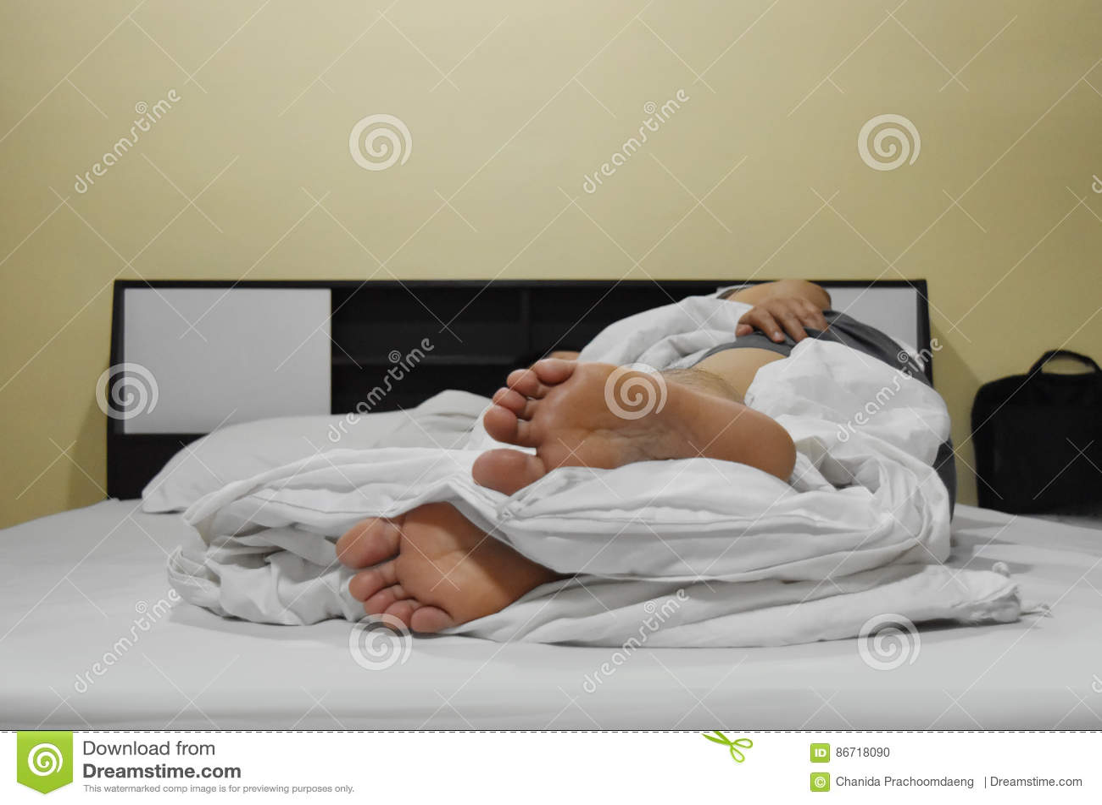 Lit Pour Jeune Homme pied d'un jeune homme se trouvant sur le lit photo stock