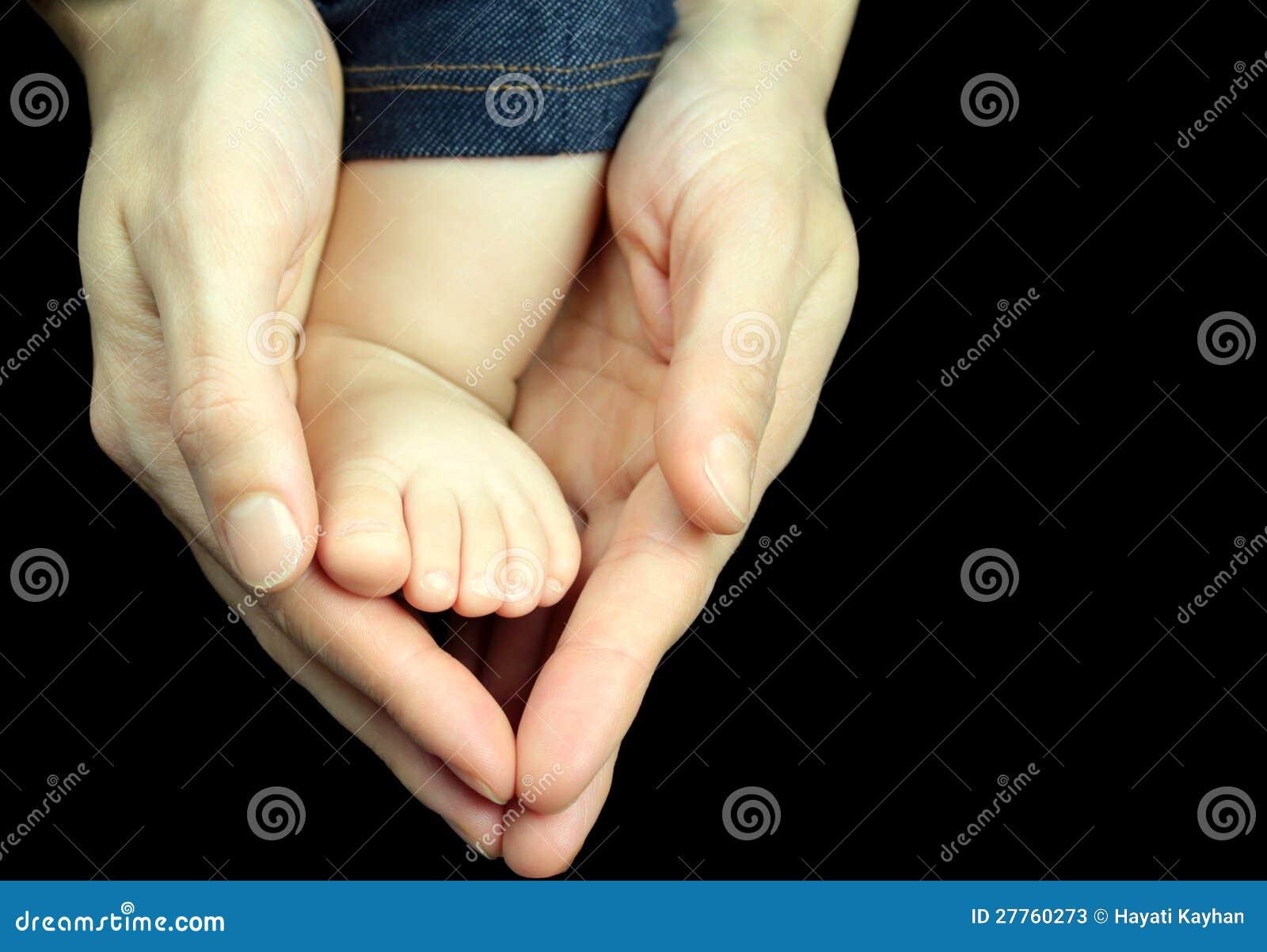 Pied de chéri dans des mains de mère sur le fond noir.