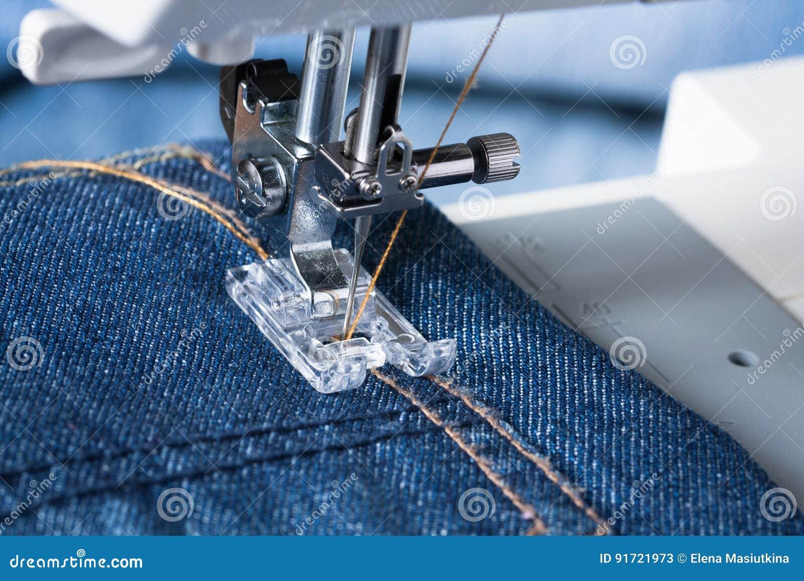 Piede della macchina per cucire sul tessuto dei jeans
