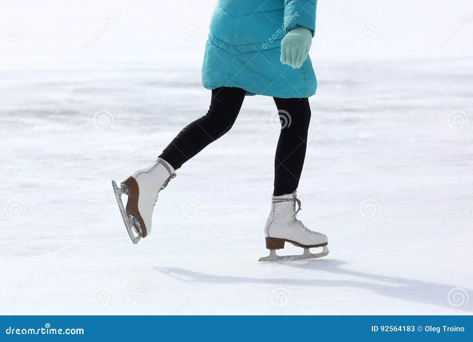 Piedi che pattinano sulla pista di pattinaggio sul ghiaccio