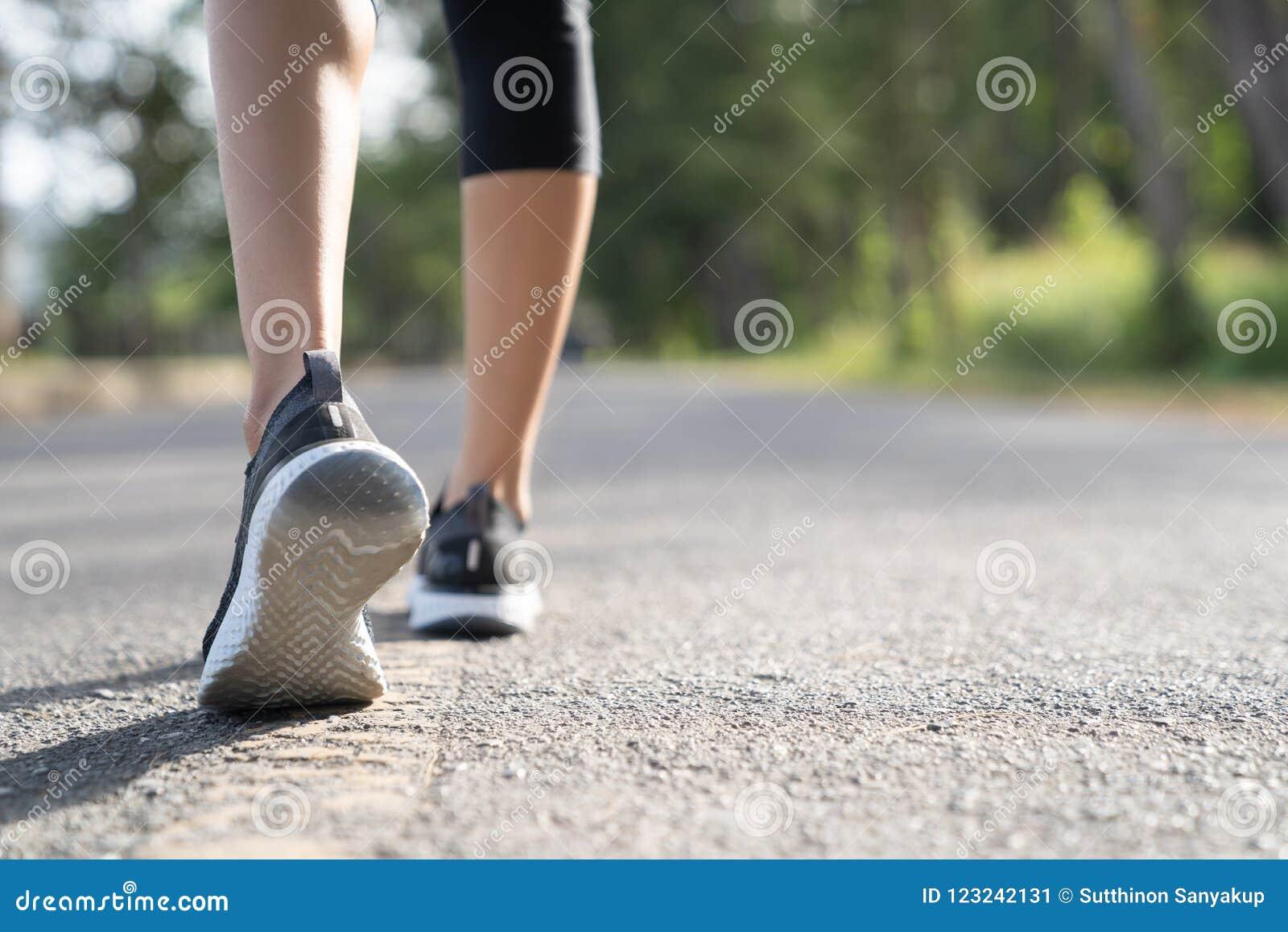 Piedi del corridore che funzionano sul primo piano della strada sul pattino Concetto di welness di allenamento di trotto di alba