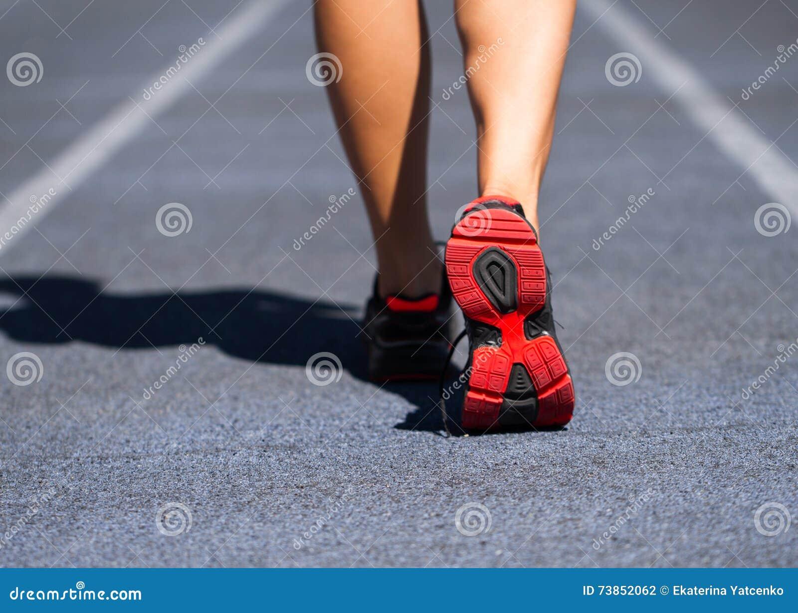 Piedi del corridore che funzionano sul primo piano della strada sul pattino Trotto w di forma fisica della donna