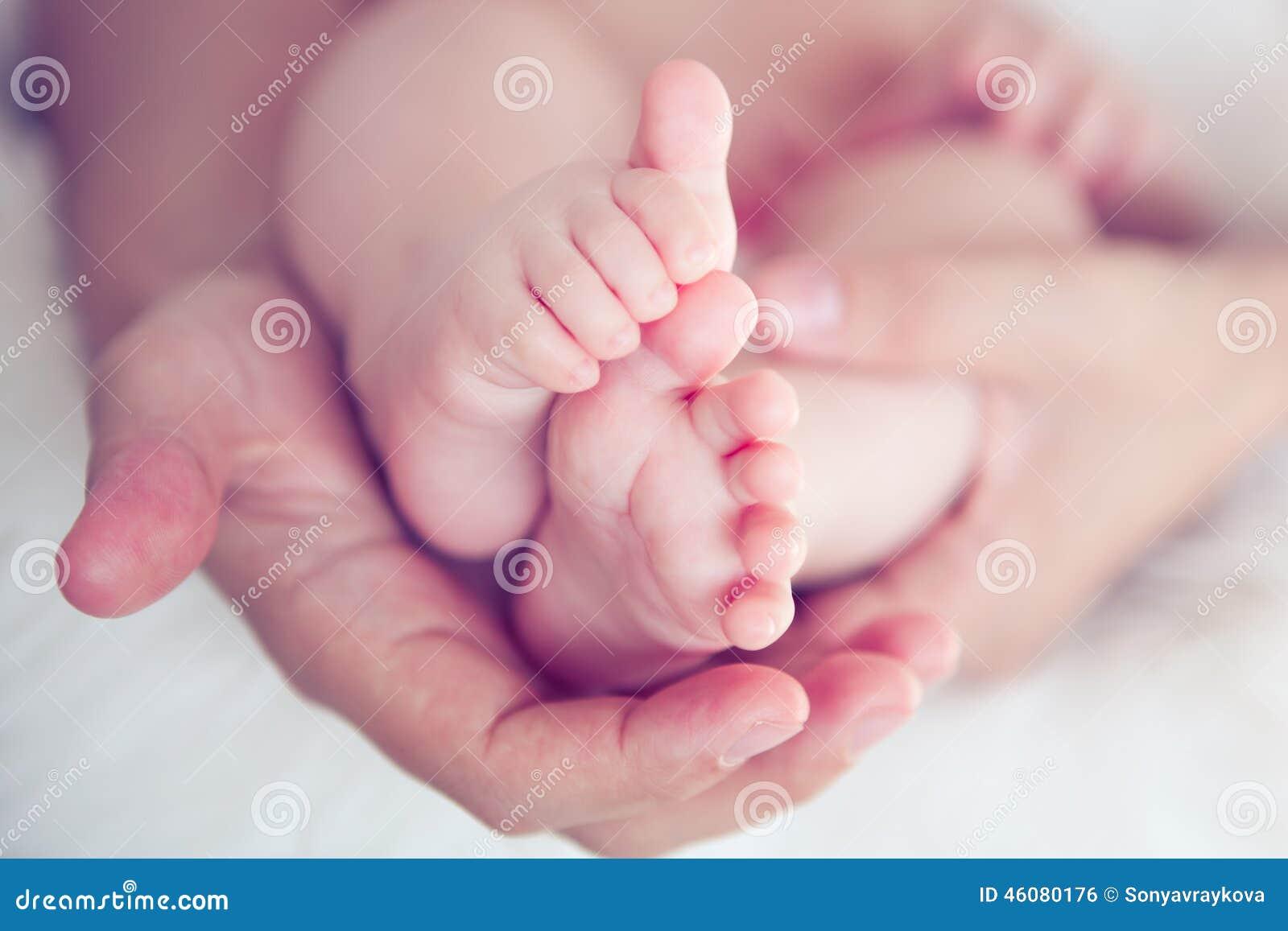 Piedi del neonato in mani della mamma