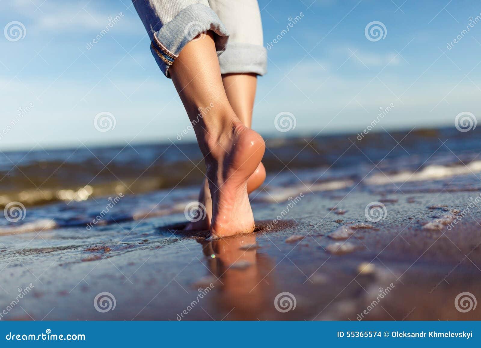 Piedi della donna nelle onde del mare