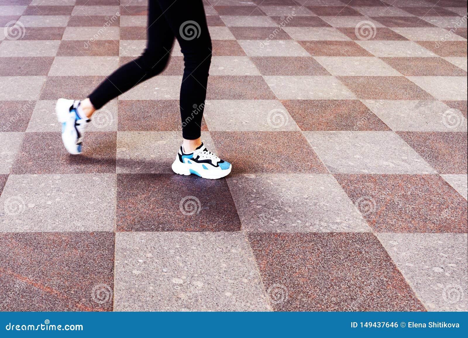 Piedi di ragazza in scarpe da tennis, camminanti sulle mattonelle di pietra