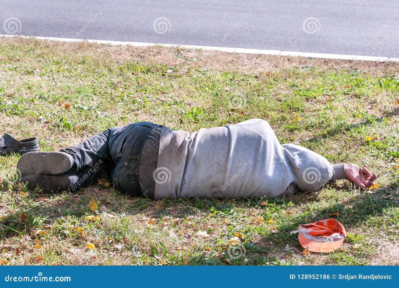 A piedi nudi bevanda uomo sporco anziano del senzatetto o del rifugiato del tossicomane o che dorme sull erba nel concetto docume