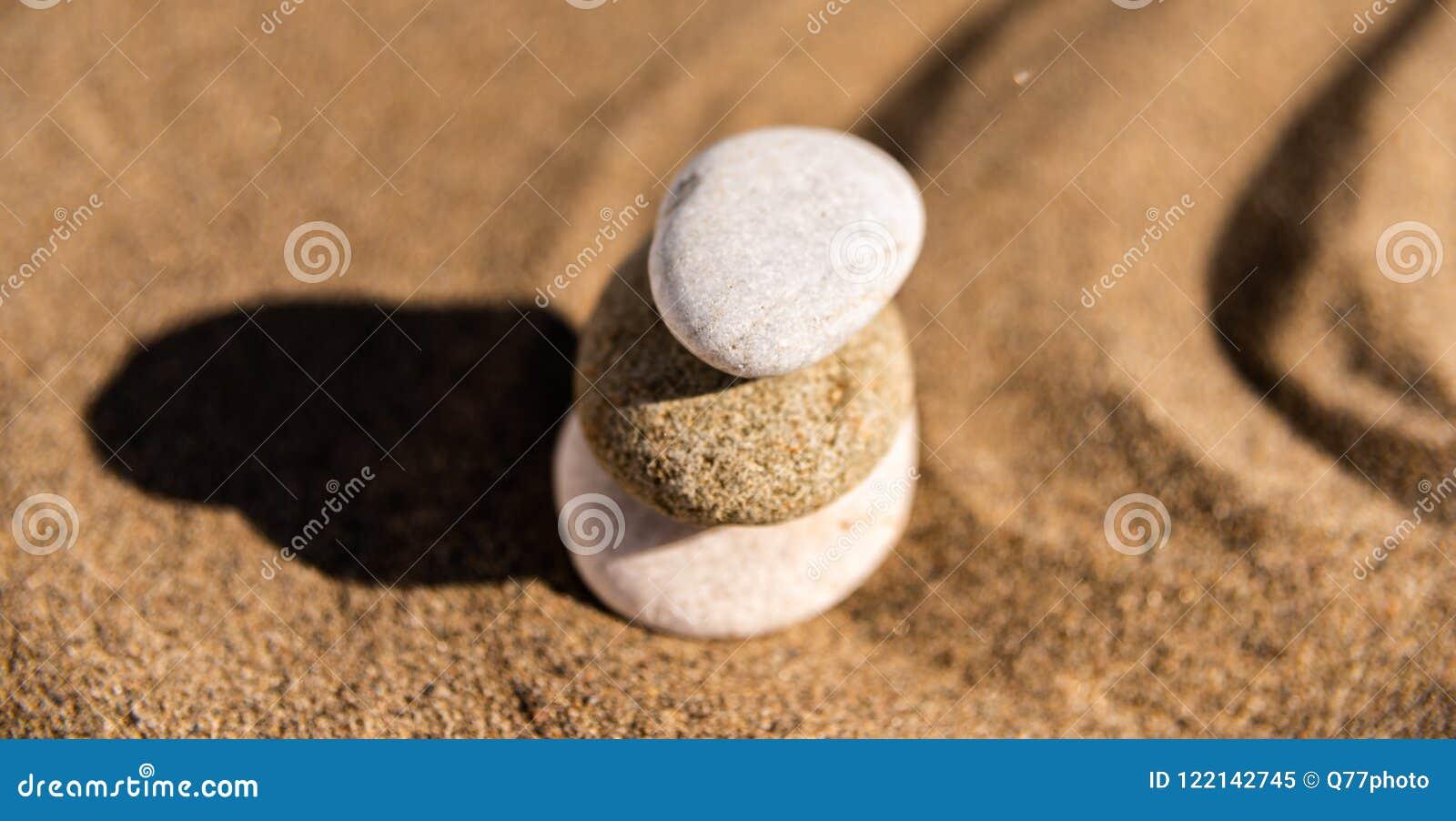 Piedra de la meditación del zen en arena, el concepto para la armonía de la pureza y el spi