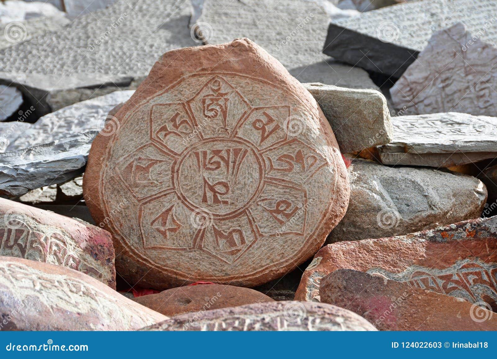 Piedras budistas del rezo con las inscripciones tibetanas y dibujos rituales en el rastro de la ciudad de Dorchen alrededor del m