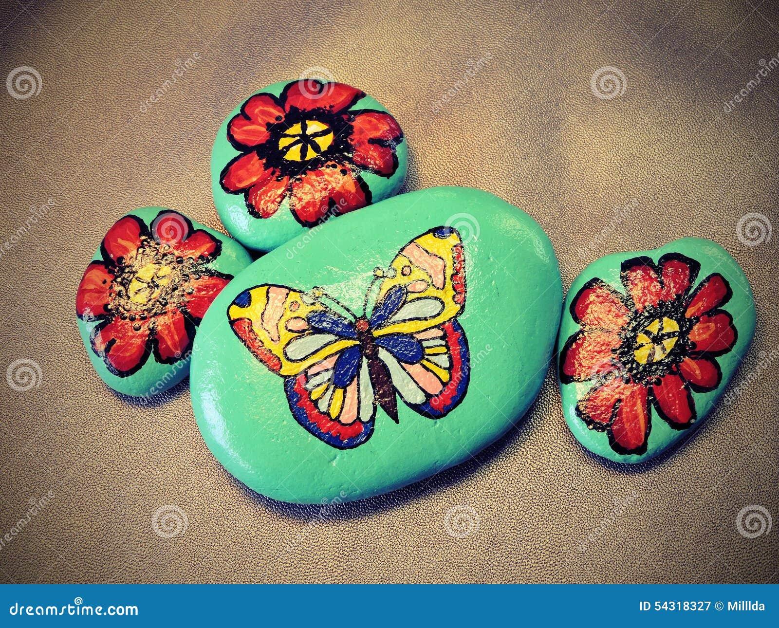Piedras con la mariposa y las flores pintadas stock de for Pintura para pintar piedra natural
