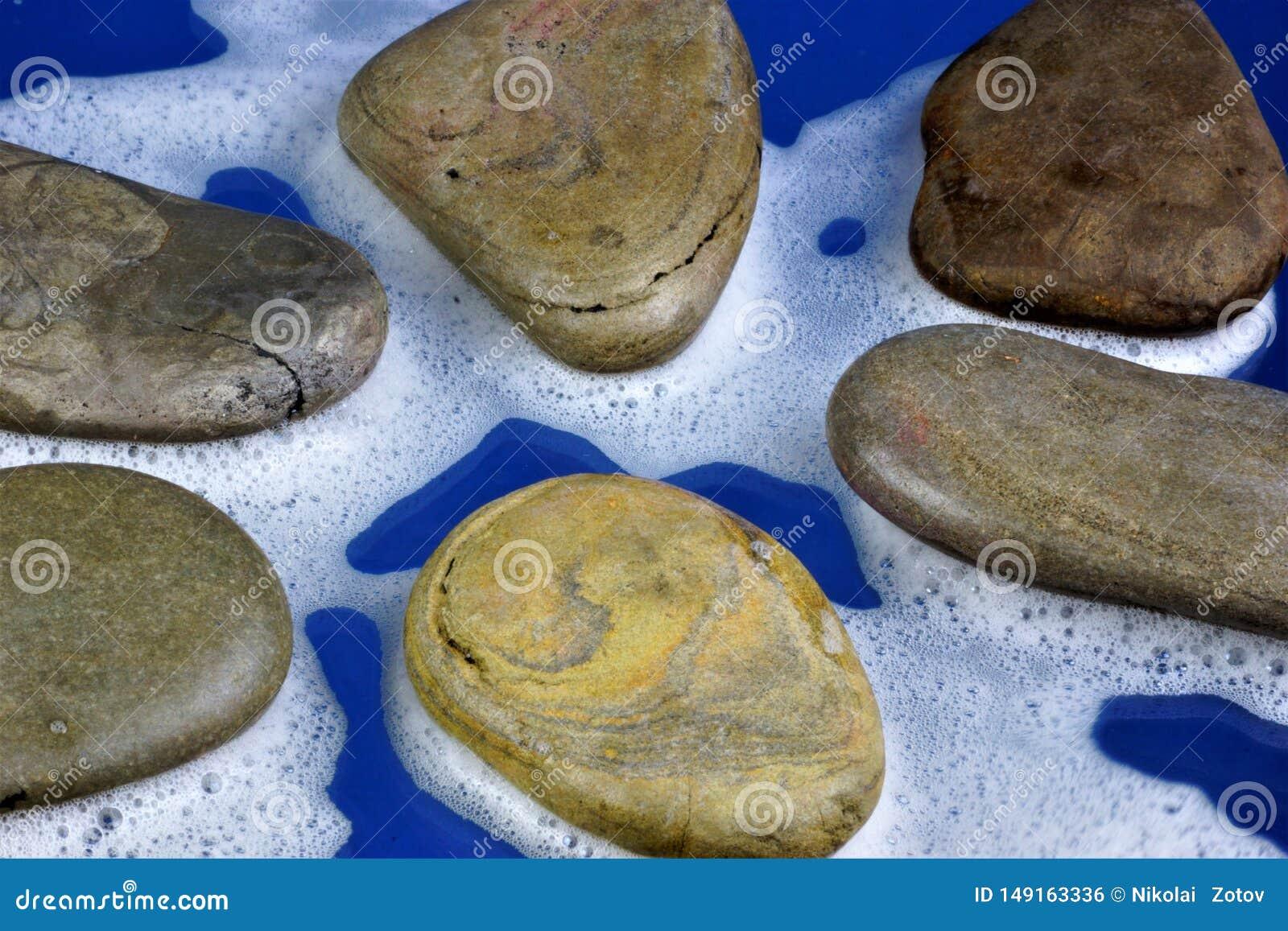 Piedras en la espuma blanca, fragmentos agua-mojados del mar de piedras del origen natural, en un fondo azul Las piedras se utili