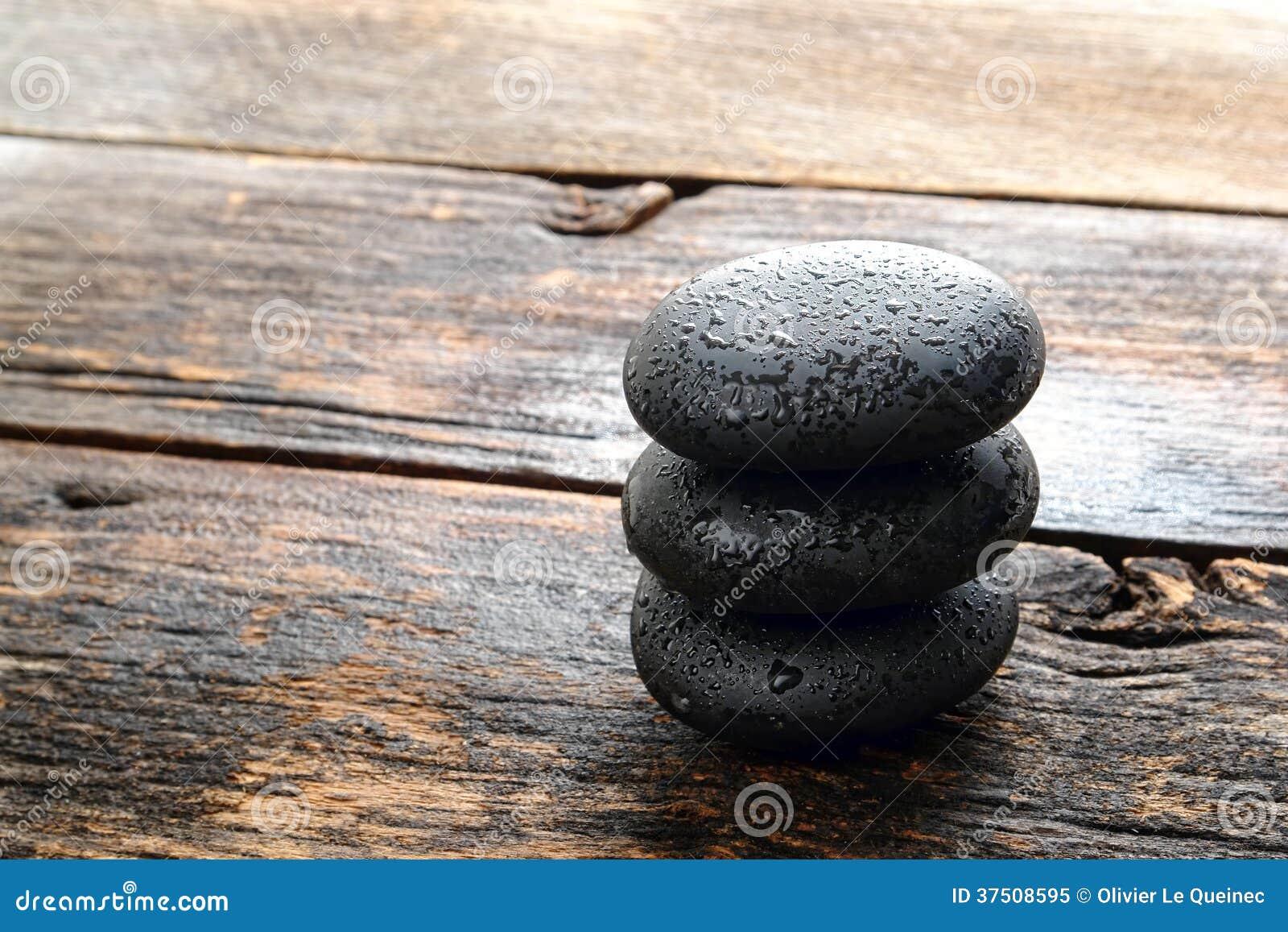 Piedras pulidas negras mojadas del masaje en la madera antigua