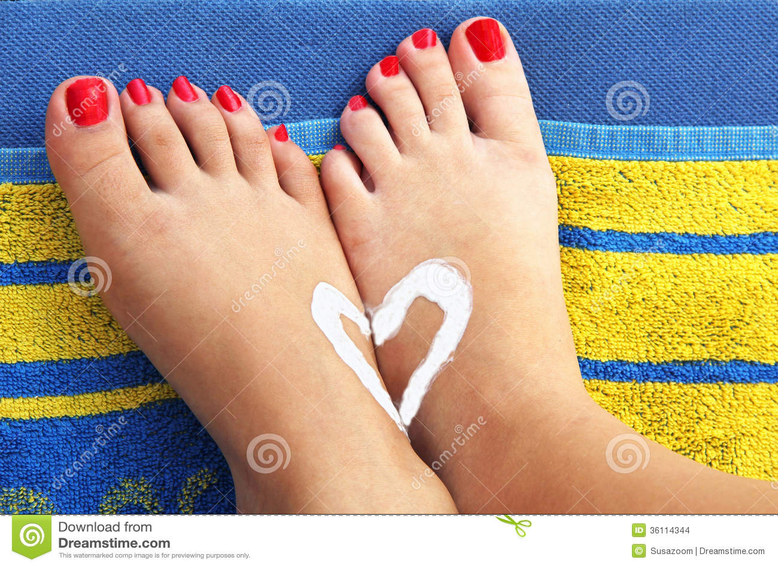 Pieds Dadolescentes Sur Une Serviette De Plage Avec Le Coeur De Sunlotion Photo Stock -4201