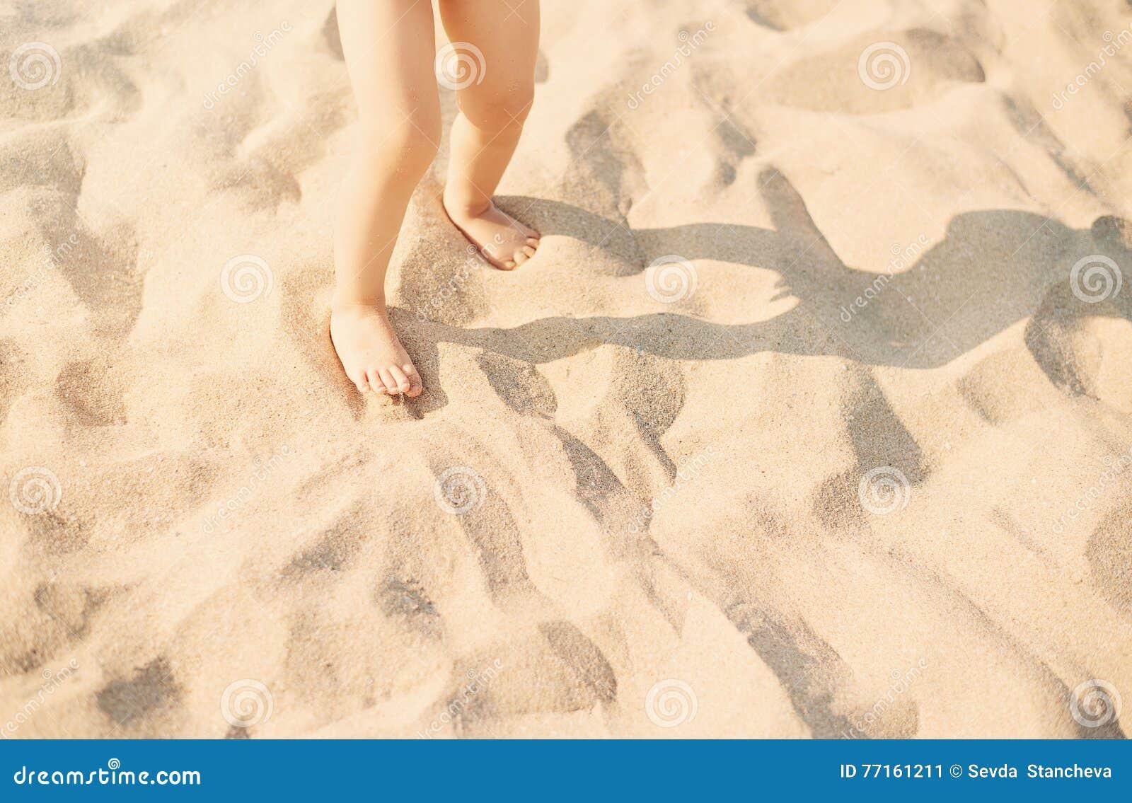 Pieds d enfant de bébé en plage de sable ? Enfant jouant en sable blanc de plage dans le jour ensoleillé Pieds de Sandy sur la pl