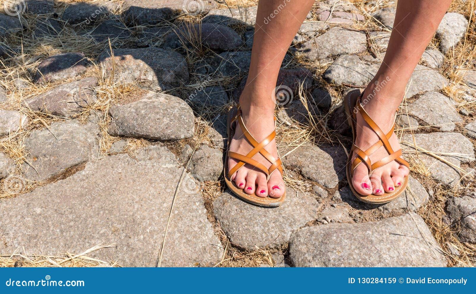 Pieds en sandales avec le poli ébréché d ongle de pied
