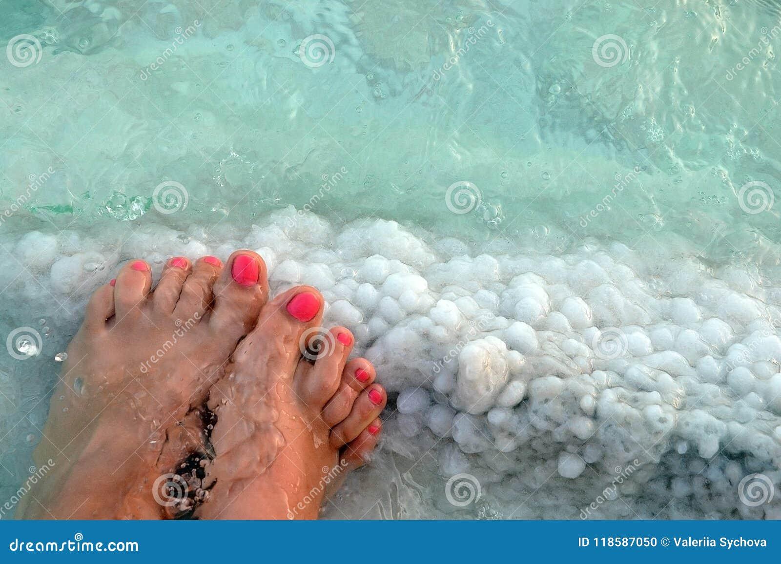 Pieds femelles avec la manucure sur la pierre, couverte de formations de sel entre les vagues dans l eau Cristallisation de sel s