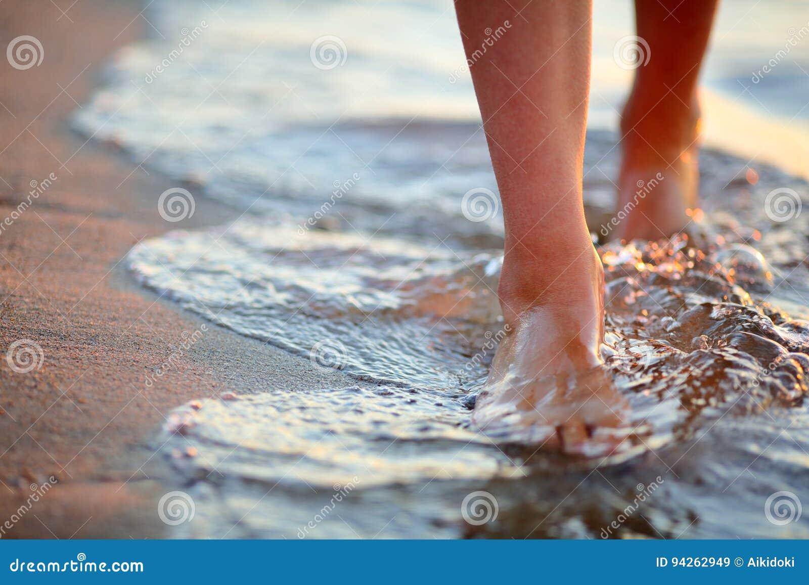 Pieds femelles d étape sur la vague de mer
