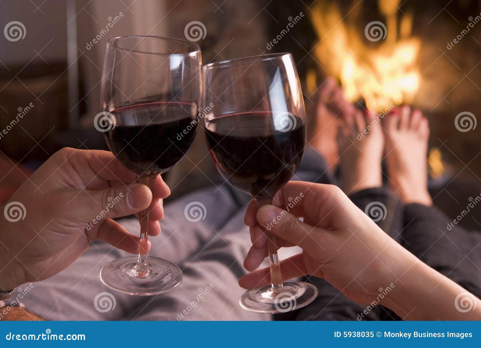 Pieds réchauffant à la cheminée avec des mains retenant le vin
