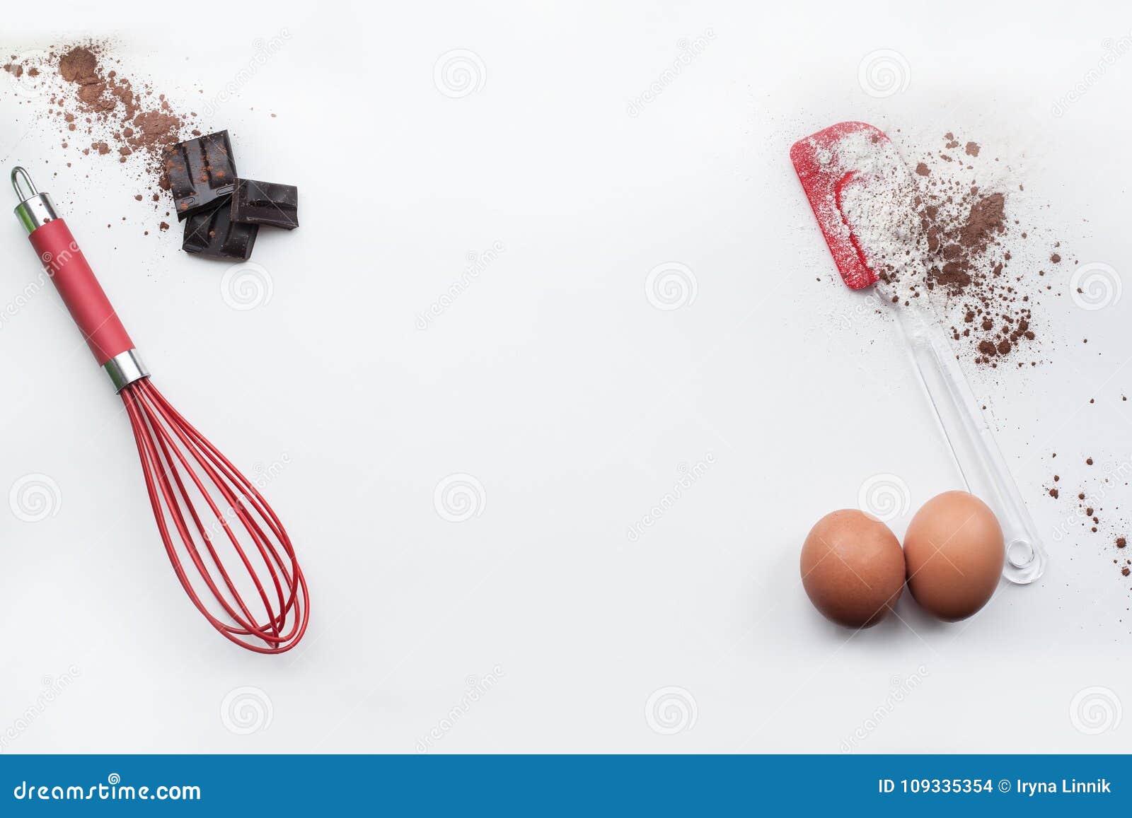 Piekarnia składniki - mąka, jajka, kakao, czekolada na bielu stole Słodkiego ciasta wypiekowy pojęcie Mieszkanie nieatutowy, kopi