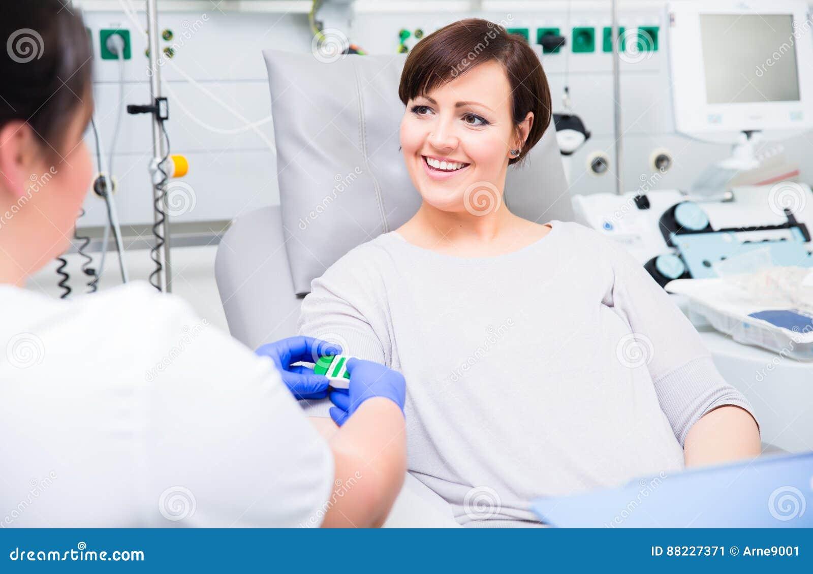 Pielęgniarka w szpitalnym sprawdza dostępie przy kobieta krwionośnym dawcą