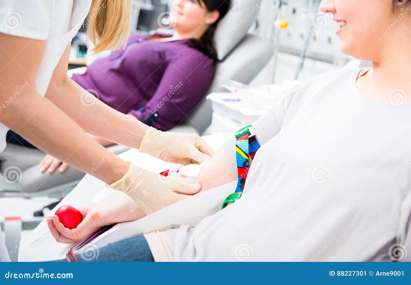 Pielęgniarka wewnątrz w dziale bierze krew od kobieta dawcy