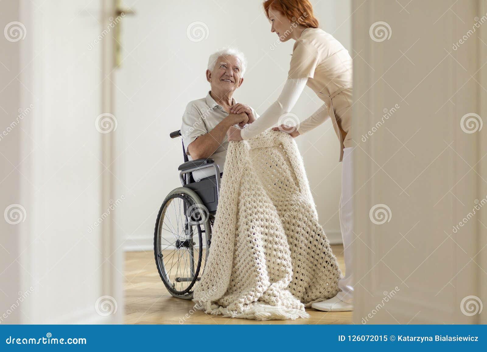 Pielęgnuje brać opiekę szczęśliwy starsza osoba mężczyzna w wózku inwalidzkim w jego ho