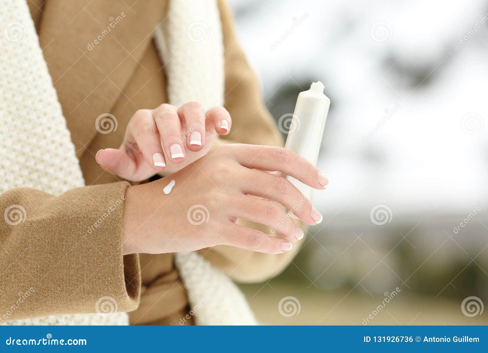 Piel de hidratación de la mano de la mujer que aplica la crema en invierno