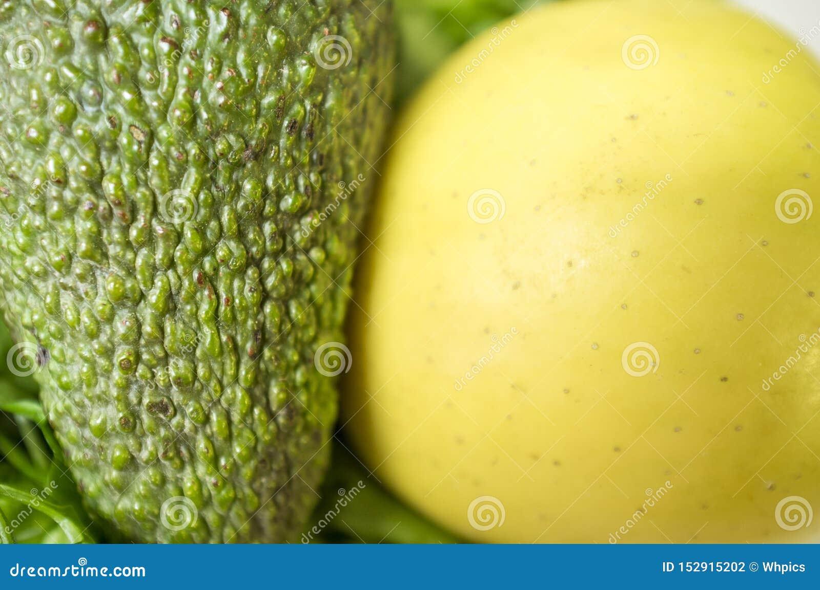 Piel suave de la manzana amarilla cerca de la piel áspera del avocato sobre el perejil fresco verde