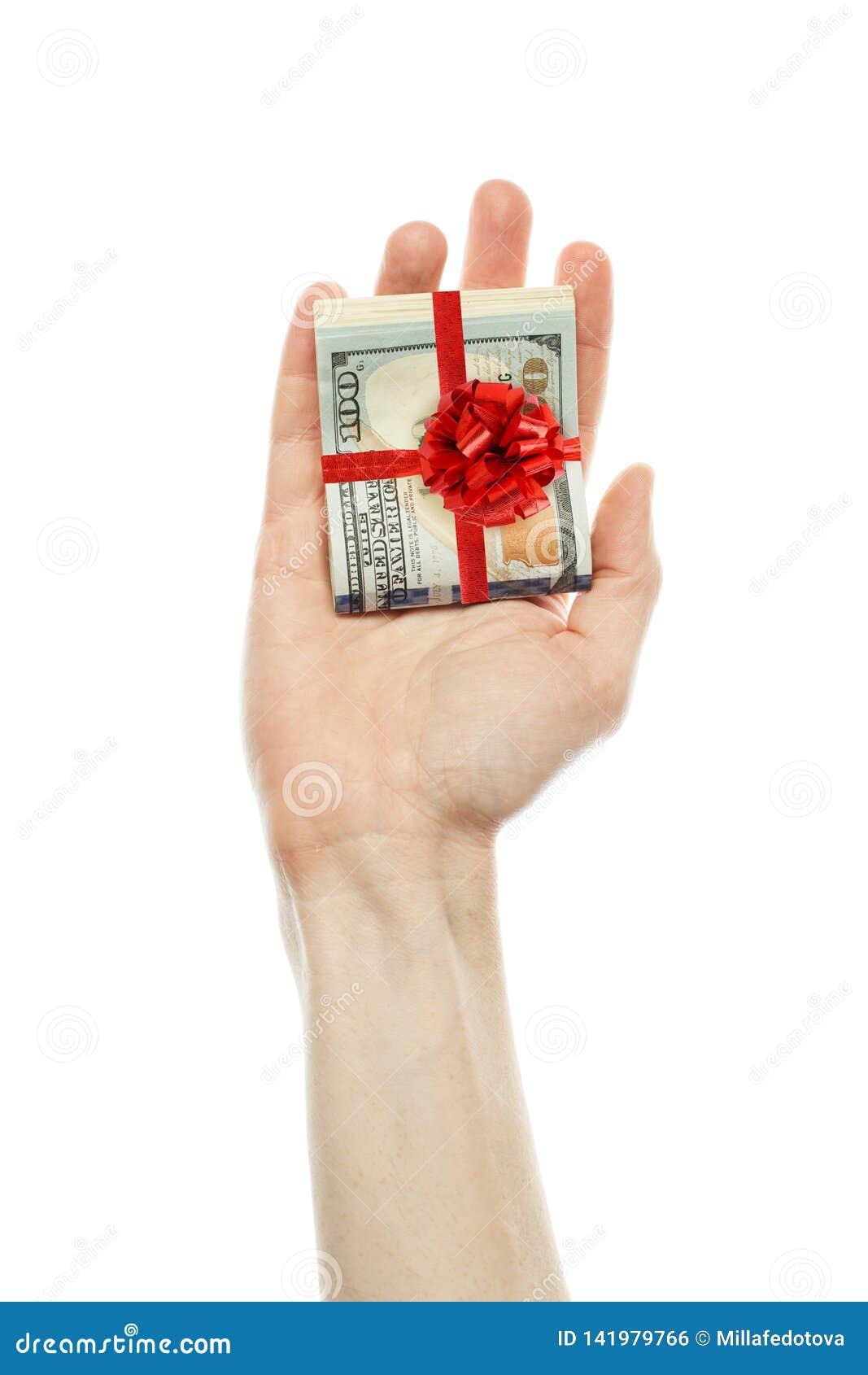 Pieniądze prezent Amerykańscy dolary gotówki z czerwonym faborkiem w męskiej ręce odizolowywającej na białym tle USA dolarów 100