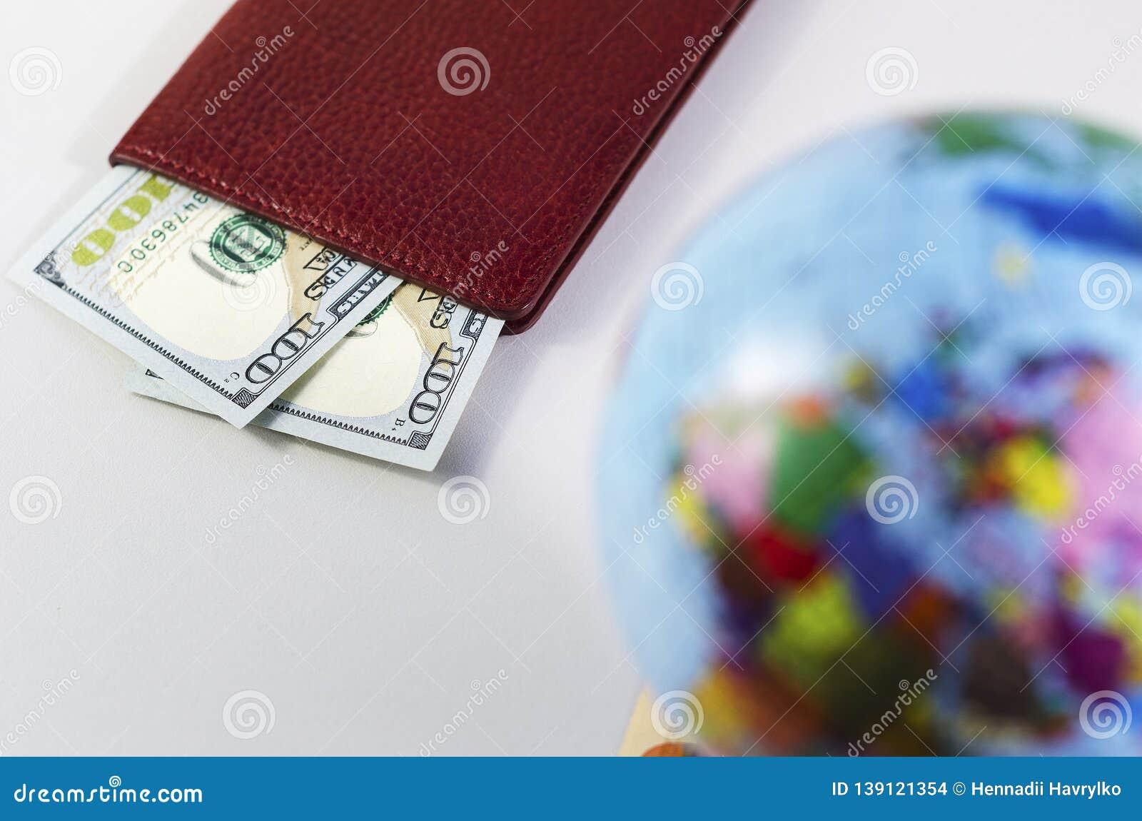 Pieniądze wśrodku paszporta i kuli ziemskiej jest z ostrości