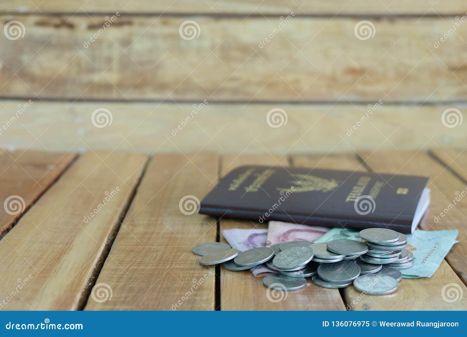 Pieniądze oszczędzania pojęcie dla wakacje z monety stertą i paszport na drewnianych tło,