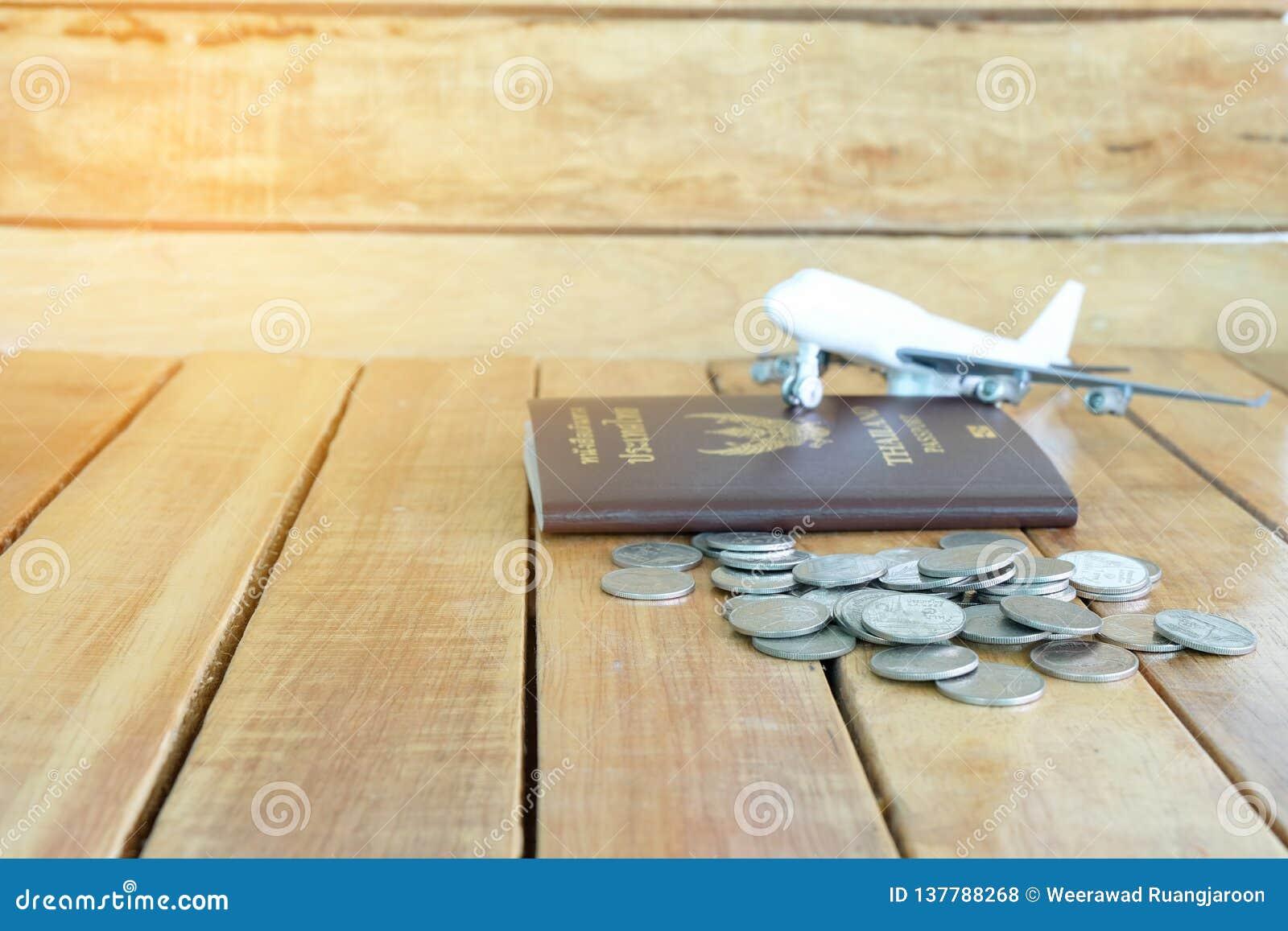 Pieniądze oszczędzania pojęcie dla wakacje z monety stertą, paszportem i samolot zabawką na drewnianych tło,