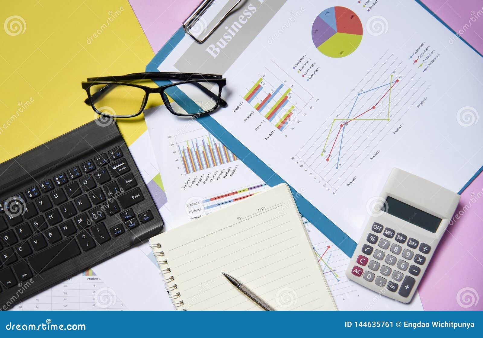 Pieniężnego i biznesowego wykresu mapy raportu papierowy dokument z kalkulatora notatnika otwartym papierem