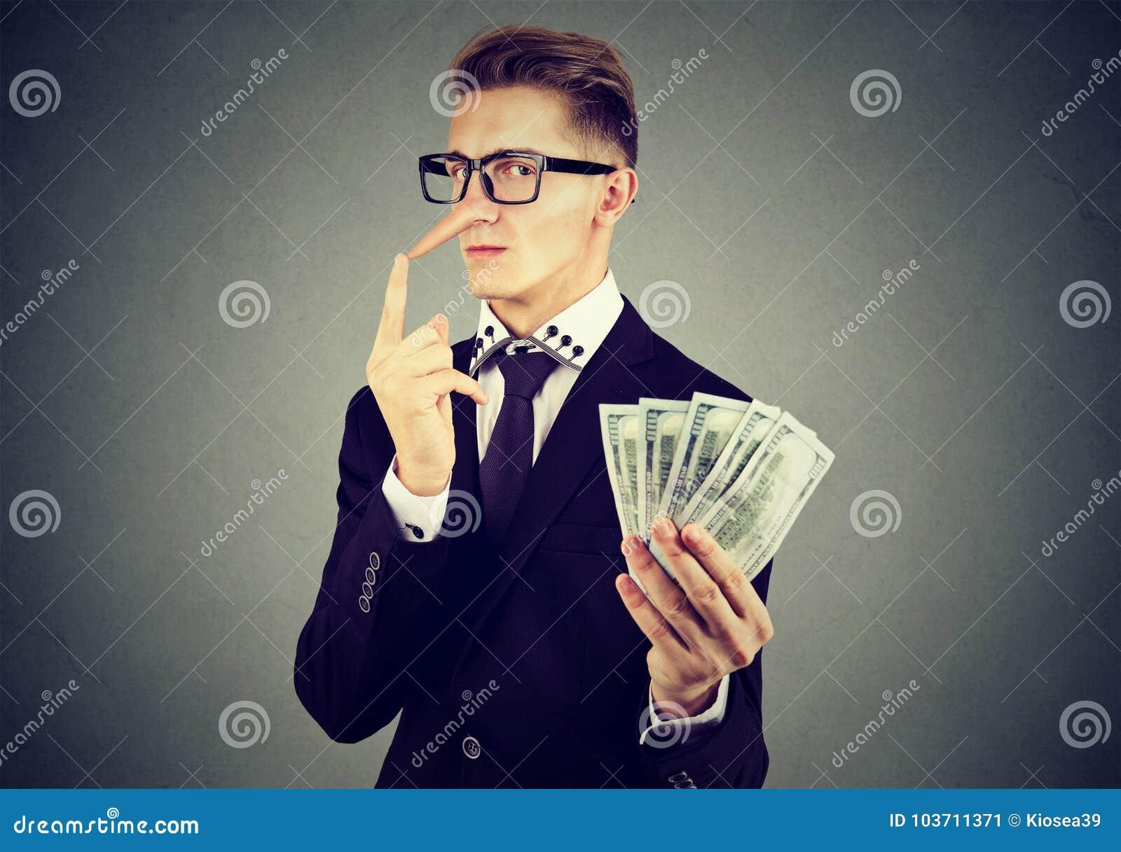Pieniężny oszustwa pojęcie Kłamca biznesowy mężczyzna w kostiumu i szkłach z dolar gotówką