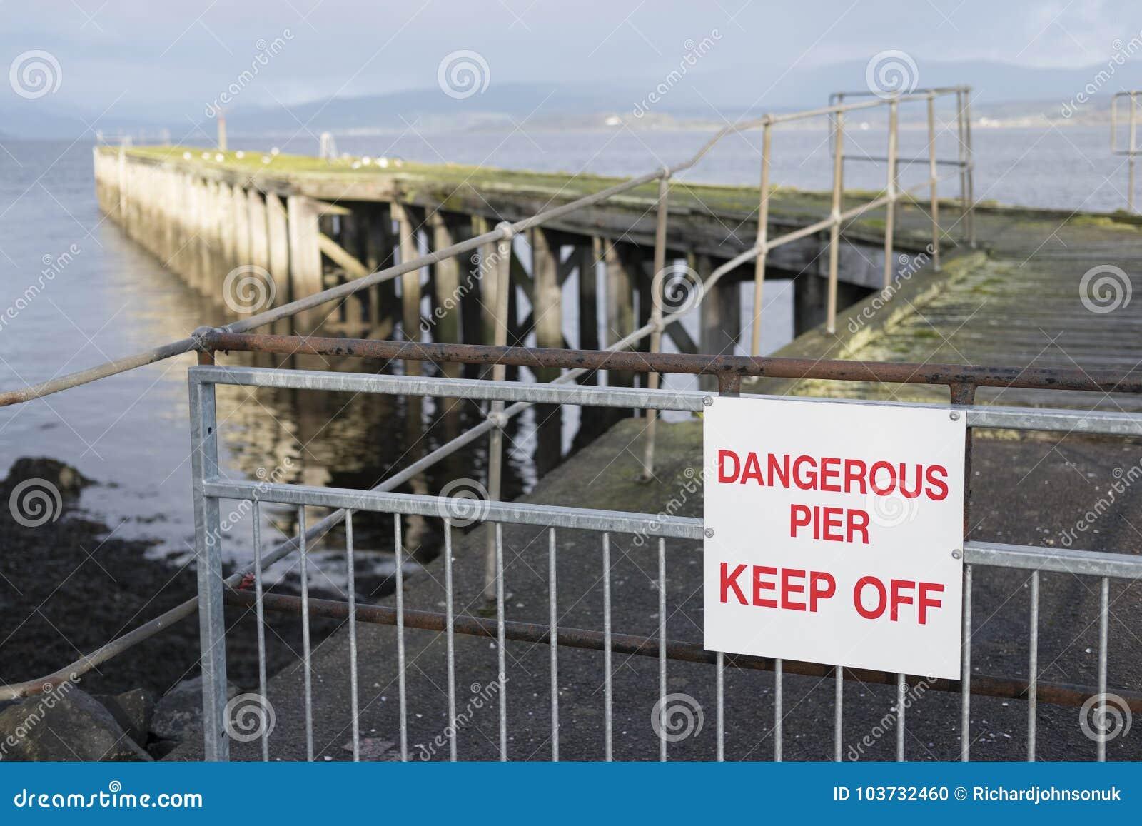 Pier Jetty Derelict Rotten Wooden dangereux retiennent le signe par la plage de mer