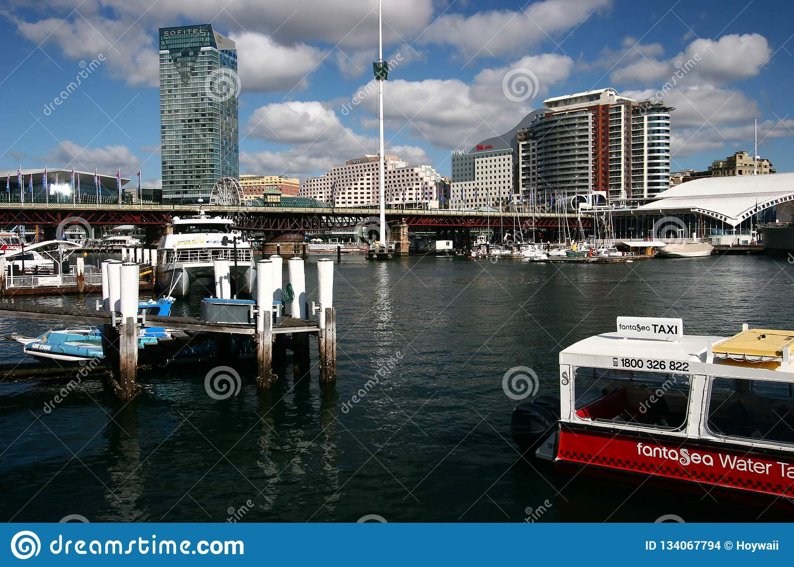 Pier with mooring posts, anchored boats, Pyrmont Bridge and city harbor waterfront with iconic cityscape in Sydney Darling Harbour
