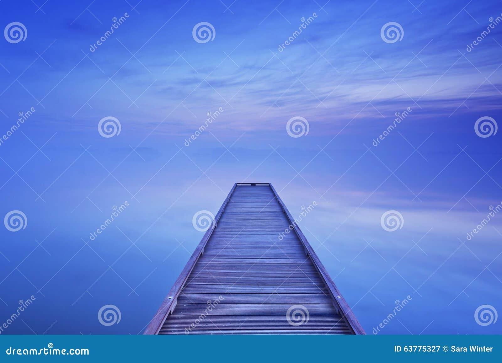 Pier op een stil meer bij dageraad in Nederland