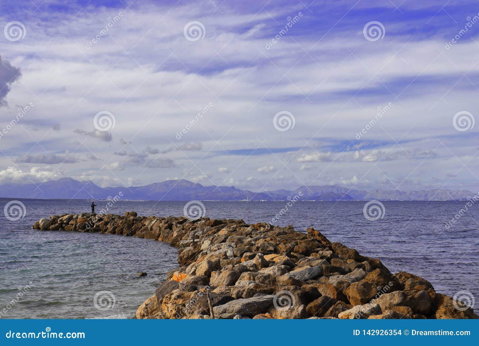 Pier/pijler van rotsen met mens visserij en bergachtergrond, Middellandse Zee, Mallorca, Spanje