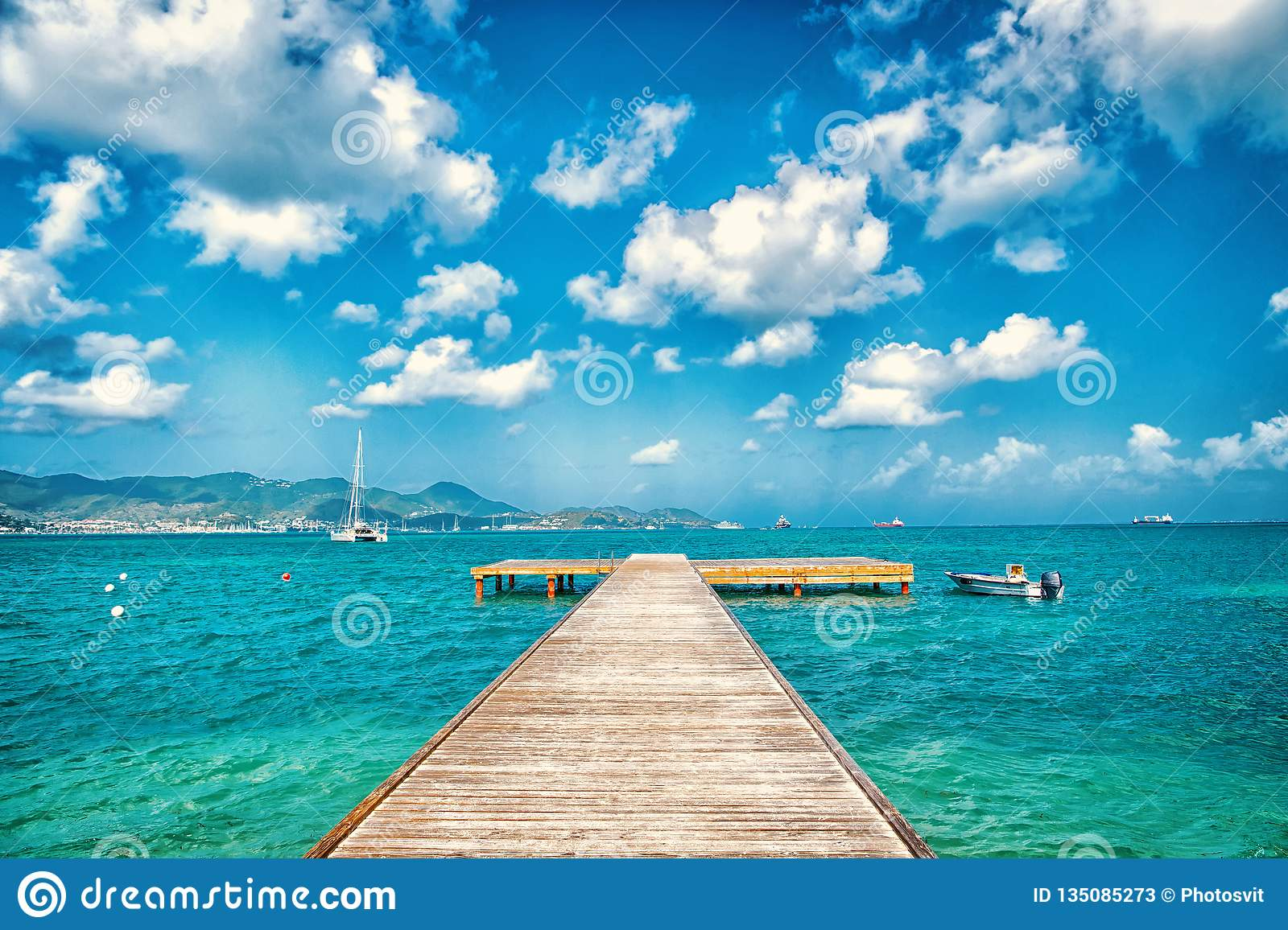 Pier in turquoise sea and blue sky with white clouds in philipsburg, sint maarten. Freedom, perspective and future