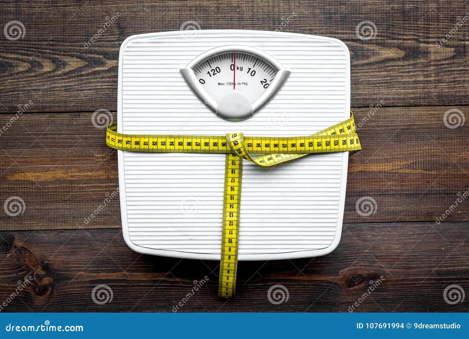 Pierda el concepto del peso Escala y cinta métrica en la opinión superior del fondo de madera oscuro