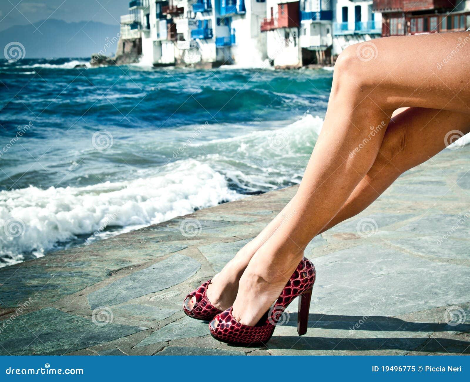 Piernas atractivas del verano por el mar
