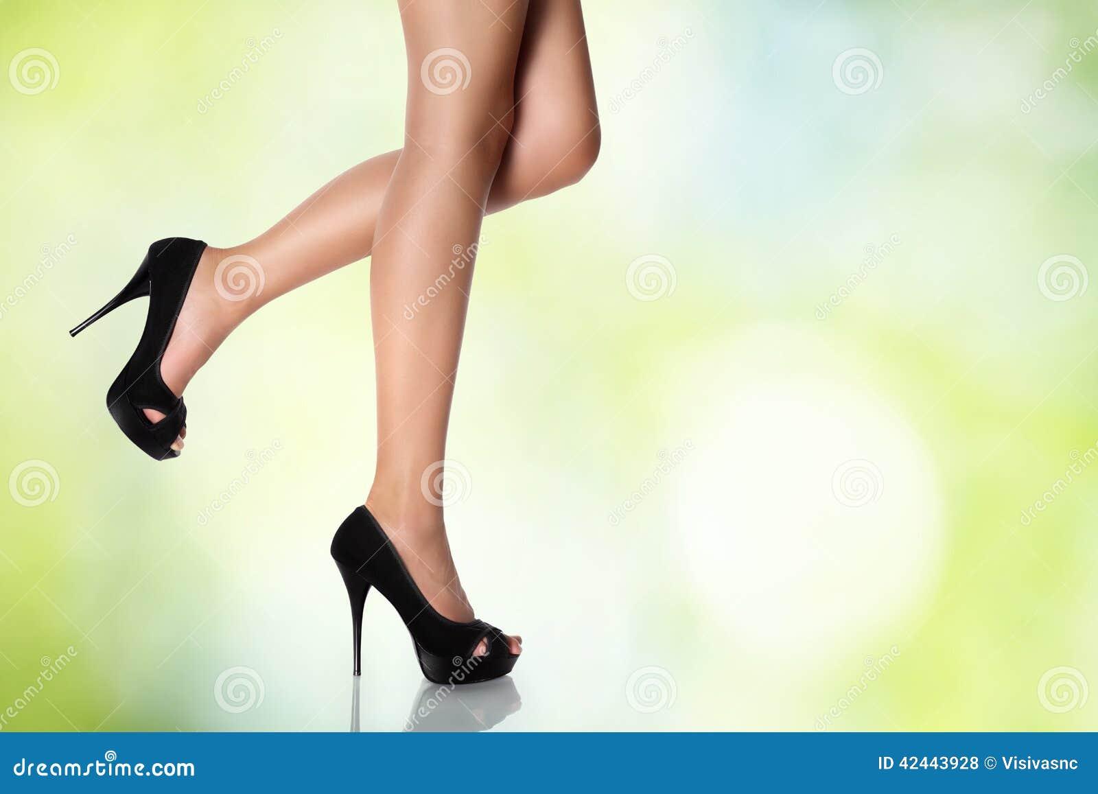 Piernas con los zapatos de tacón alto negros en un fondo verde
