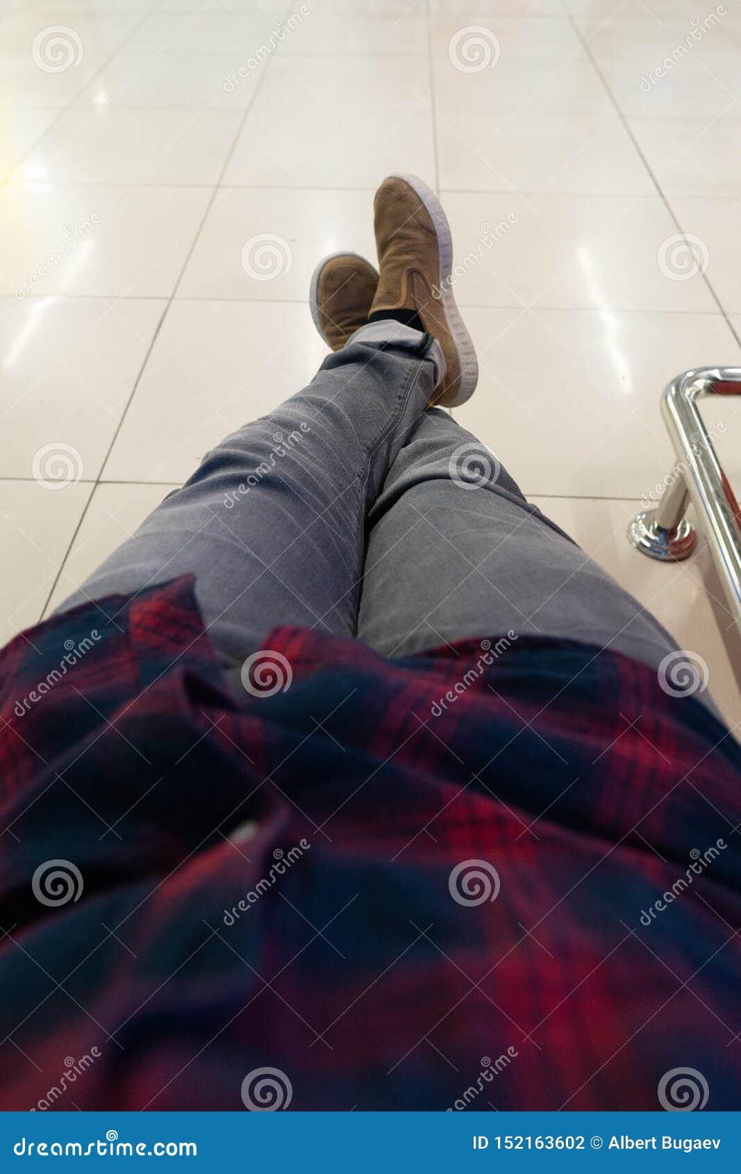 Piernas cruzadas de un hombre en pantalones grises y zapatos marrones El hombre en la sala de espera