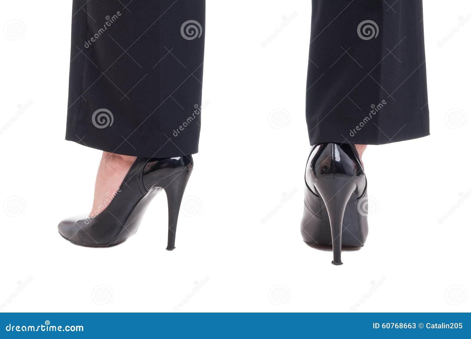 40c235e8ad08 Piernas de la mujer de negocios que llevan los zapatos de cuero negros con  los tacones altos aislados en el fondo blanco del estudio