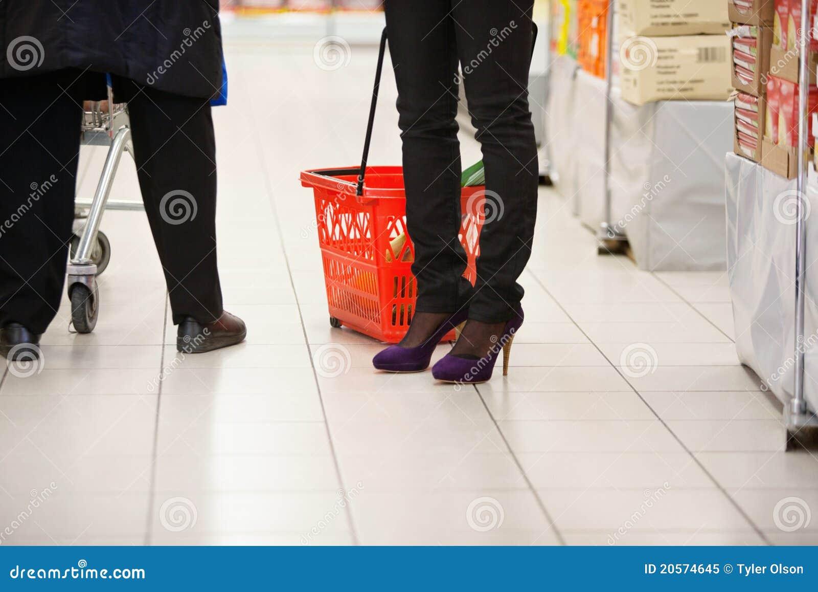 Piernas de los compradores en supermercado