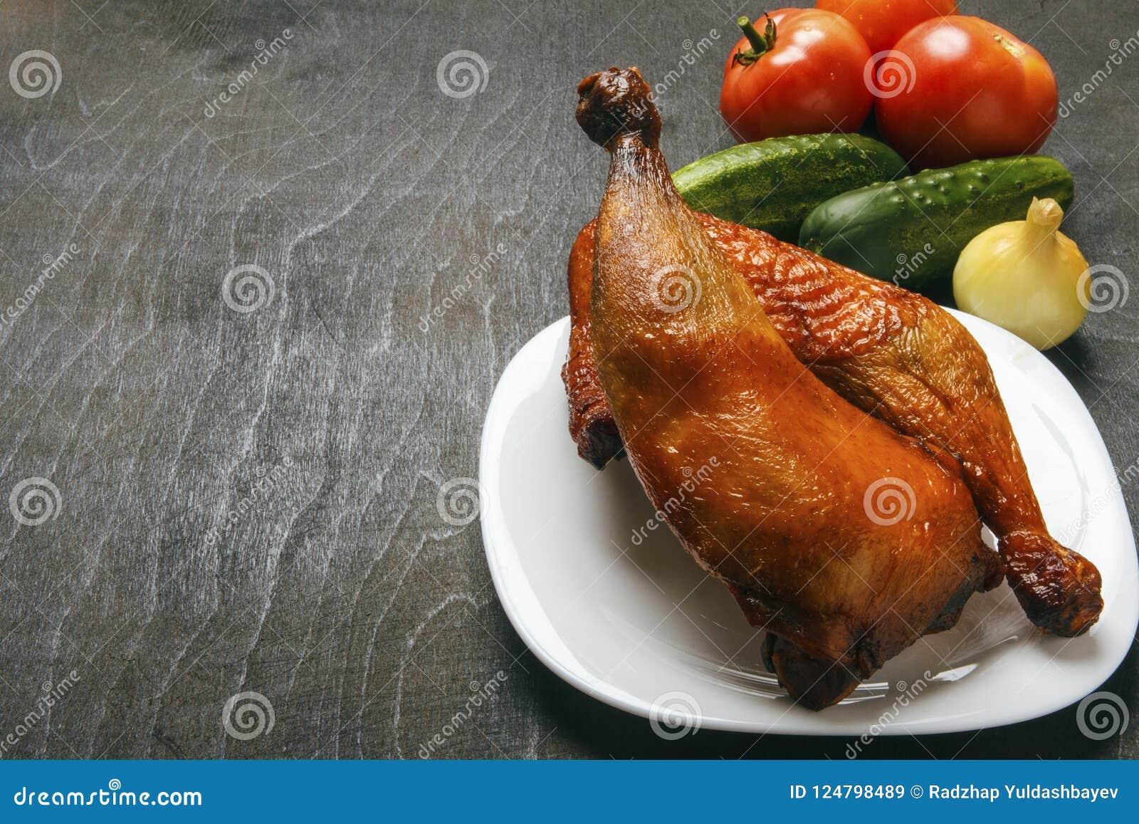 Piernas de pollo de aves de corral, cocinadas en una parrilla en una placa blanca Verduras orgánicas frescas en un fondo negro Co