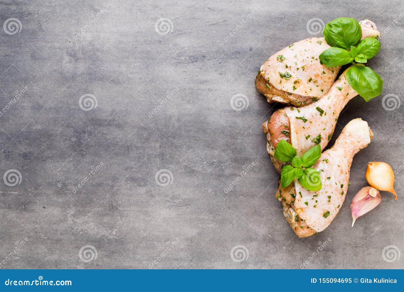 Piernas de pollo picantes, verduras frescas en un fondo gris Visi?n superior
